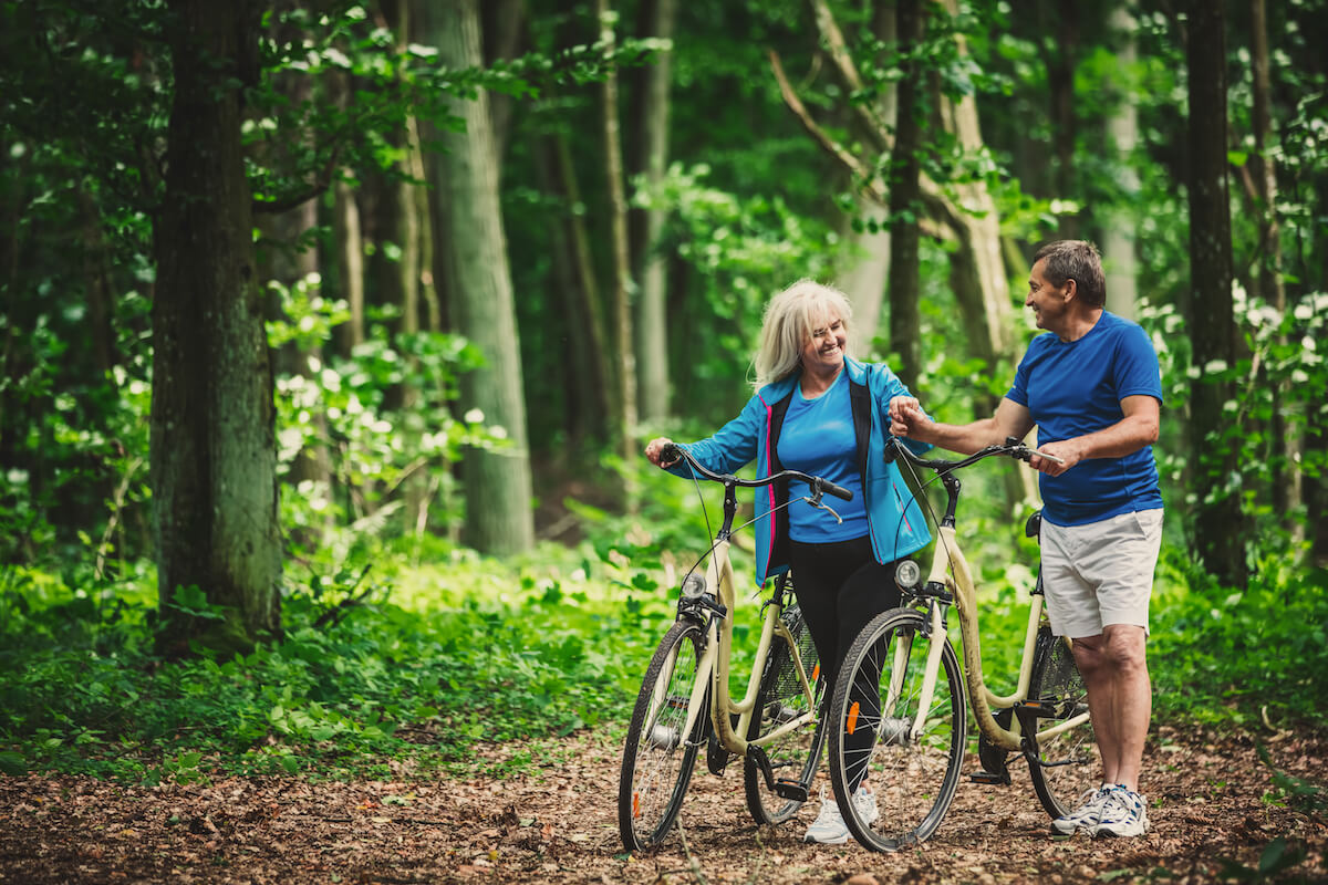 Retired Couple Walking With Bikes In The Forest.