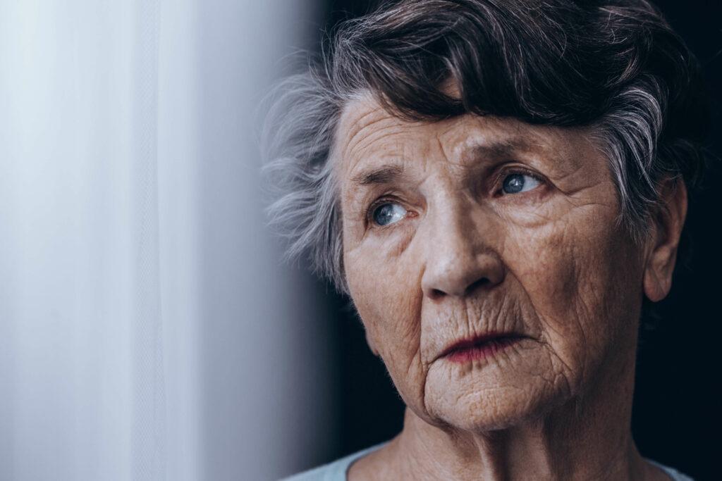 Portrait of despair, old woman standing beside window