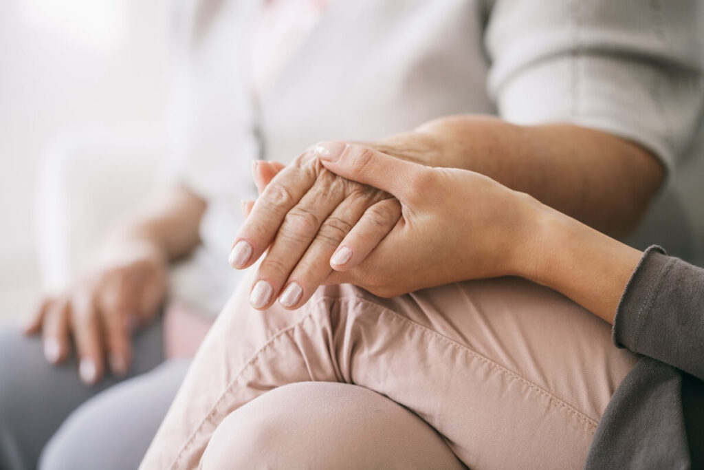 Close up of caregiver holding woman's hand